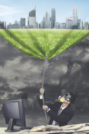 Go Green concept: Businessman with mask pulling a banner with better work environment picture