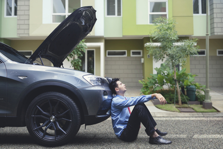 Frustrated businessman feeling hopeless leaning on his breakdown car Stockfoto