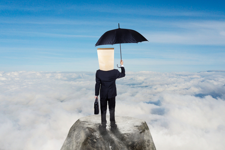 Business concept: Unknown businessman carrying umbrella on top of mountain