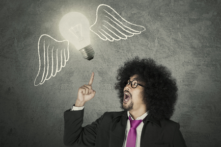 Afro businessman getting and idea represented with light bulb flying with wings Archivio Fotografico