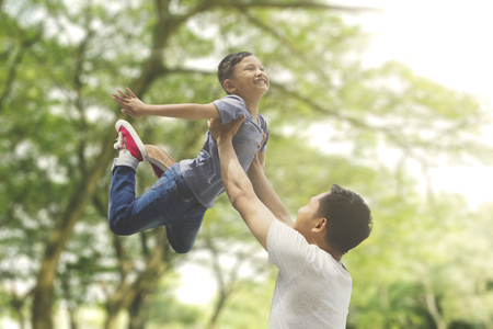 Asian family spending spring concept: a father lifting son with blur tree background Stock Photo