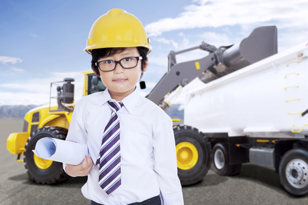 Cute boy with safety helmet and blue print in front of an excavator loading truck with soil on a construction site