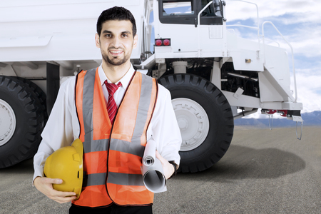 Coal mine engineer holding safety helmet and paperwork in front of a big white mining truck