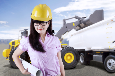Female architect or contractor standing in front of an excavator loading truck with soil on a construction site Stock Photo