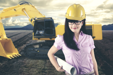 Beautiful female architect with blueprint next to a tractor on a construction site Stock Photo