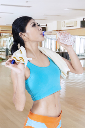 Beautiful slim Asian woman with sport wear drinking water in a group exercise room