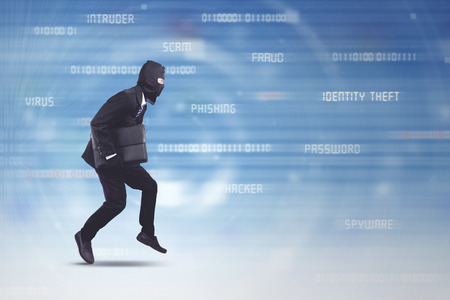 Thief wearing business suit and mask running stealing laptop over futuristic background. Hacking or computer security concept