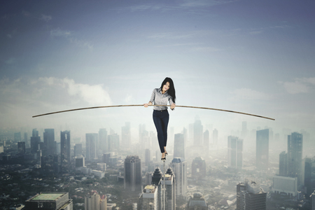 Beautiful businesswoman holding a stick to balance her body while walking on a rope. Shot above a city