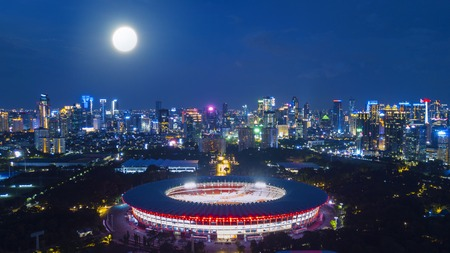 JAKARTA, Indonesia. Jan 12, 2018: Aerial view of new renovated Senayan Stadium with Jakarta skyline red for the Asian Games 2018