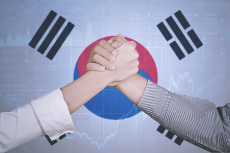Hands of business team posing partnership near a growth graph and South Korea flag. Symbolizing of peace Stock Photo