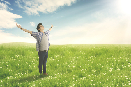 Happy man with arms wide open enjoying spring on blossom meadow. Summer or Spring concept Stock Photo