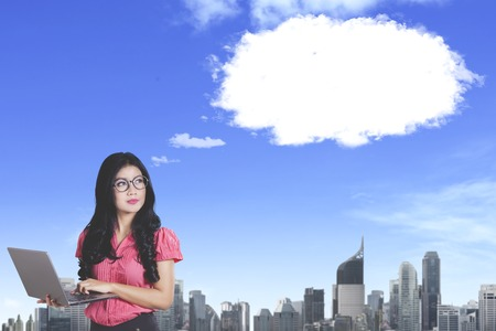 Image of pensive female entrepreneur looking up at empty cloud speech bubble in the sky