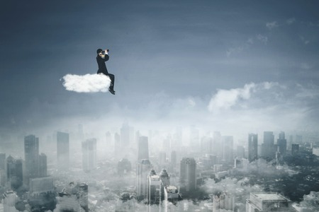 Young businessman wearing gas mask while sitting on the cloud and using binoculars  Stock Photo