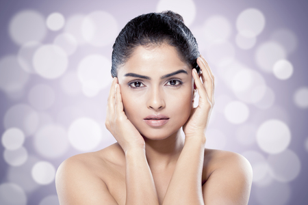 Beautiful Indian woman with healthy skin against blurred lights background. Asian beauty and skincare concept Stockfoto