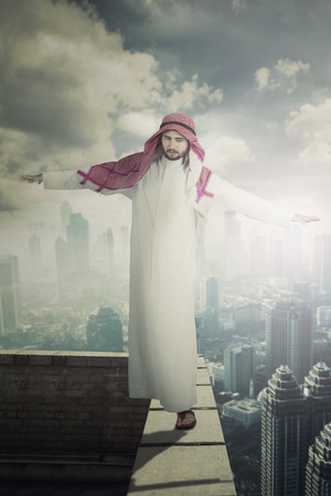 Portrait of Arabian businessman keeping his balance while walking on the rooftop