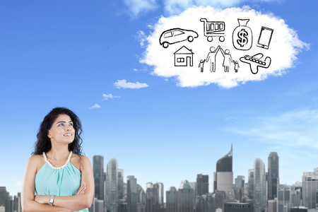 Portrait of Indian female student imagining her wishes while looking at cloud speech bubble in the sky Stock Photo