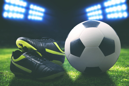 Soccer boot and ball on the field inside a stadium shot at night