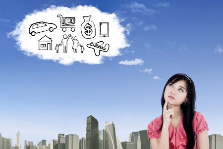 Pretty businesswoman imagining her wishes while looking at cloud speech bubble in the sky Stock Photo
