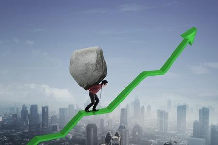 Image of Asian businessman holding big stone while walking on an upward arrow  스톡 콘텐츠