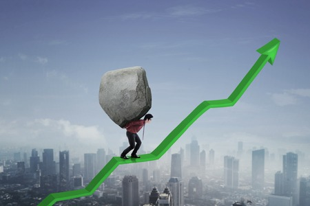 Image of Asian businessman holding big stone while walking on an upward arrow  Standard-Bild