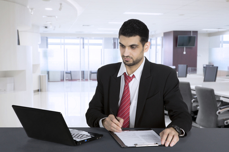 Businessman working on a business report with laptop in a modern office