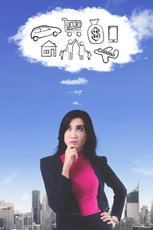 Portrait of pensive businesswoman looking at cloud speech bubble in the sky while imagining her wishes