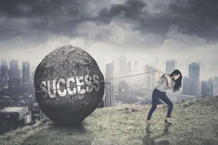 Picture of young businesswoman trying to pull success word in a stone on the mountain