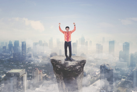 Arabian businessman expressing his success by lifting hands while standing on the mountain with modern city background