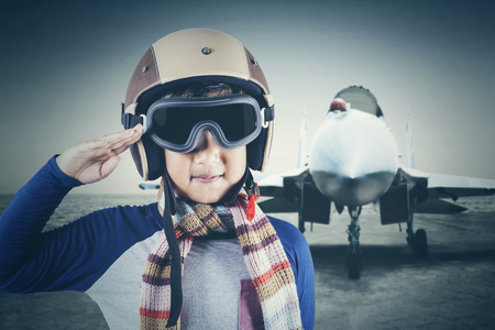 Portrait of cute little male pilot giving a respectful hand gesture with a jet plane background