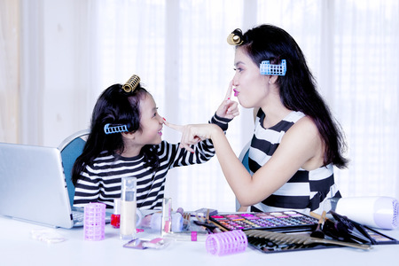 Cute daughter with hair curl playing makeover to her mother at home Stock Photo