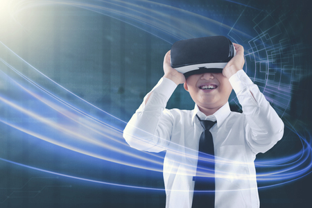 Amazed kid looking at his virtual reality headset with futuristic background