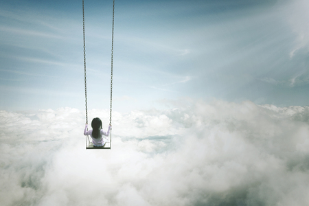 Back view of a lonely girl sitting on the swing. Shot above the clouds