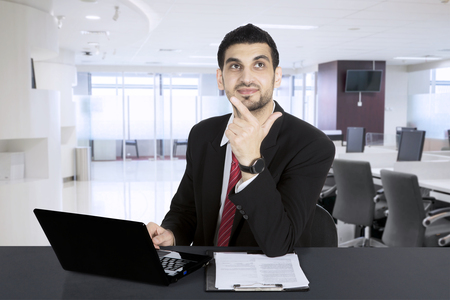 Businessman thinking while working with laptop in modern office