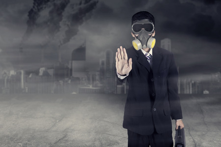 Unknown businessman wearing gas mask while showing hand gesture to stop with polluted city background