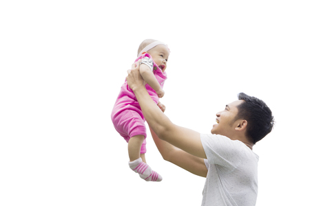 Picture of happy father lifting his baby while playing together, isolated on white background