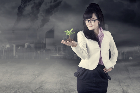 Picture of beautiful business woman holding a plant while standing in the polluted city  Stock Photo