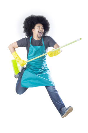 Young male cleaning service professional jumping isolated over white