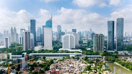 JAKARTA - Indonesia. March 12, 2018: Panoramic view of Jakarta cityscape with residential houses, modern office and apartment buildings shot from a drone at sunny day Banco de Imagens