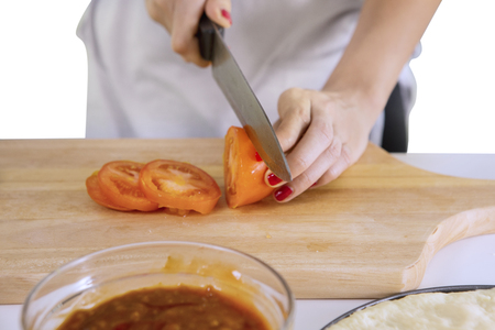 Closeup of unknown female chef slicing a tomato with knife while cooking pizza in the kitchen