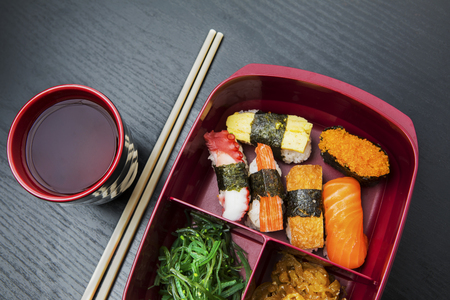 Top view of healthy food on the lunch box with chopsticks and soy sauce above table Stock Photo