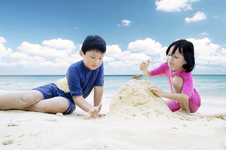 Picture of two little children looks happy while making sand castle on the beach