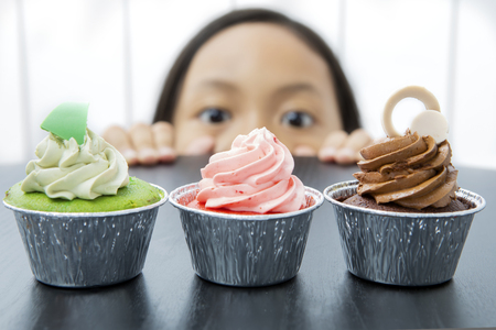 Picture of little girl is peeping tasty cupcakes on the table