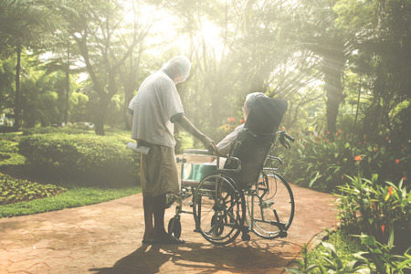 Elderly woman sitting on the wheelchair while relaxing with her husband in the park