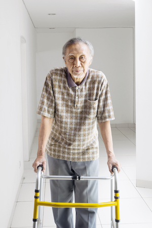 Portrait of lonely Asian elderly man walking with a walker at home