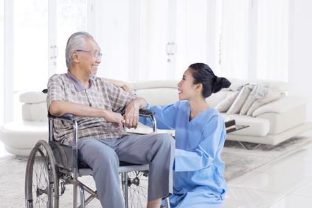 Glücklicher asiatischer älterer Mann, der mit seiner Krankenschwester spricht und lächelt, während auf Rollstuhl im Wohnzimmer zu Hause sitzt