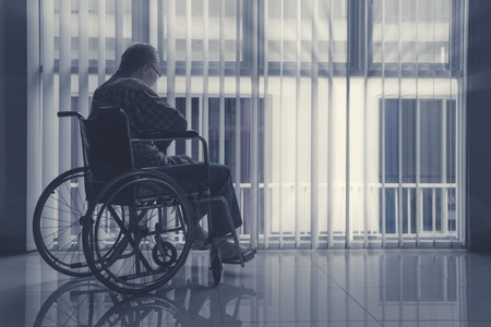 Lonely elderly man sitting on wheelchair near the window at home