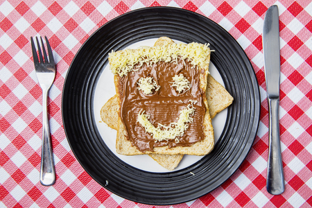 Top view of grated cheese shaped smiley face on the chocolate bread. Shot on the dining table Stock Photo