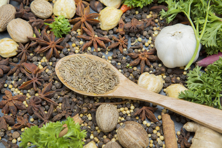 Top view of dried cumin seeds or caraway seeds in the wooden spoon with herbs and spices on the table Stock Photo