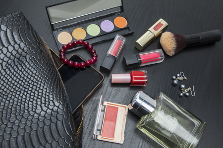 Closeup of makeup tools with smartphone and black bag on the table