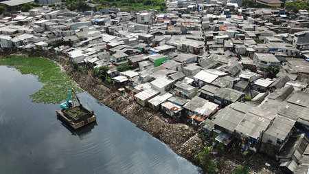 Aerial landscape of slum houses on the lakeside with an excavator removing water plant on the lake
